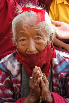 Tibetan woman praying wearing face mask to protect against the dust, and symbolic red blindfold