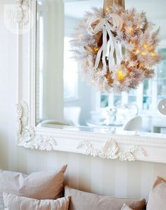 A beautiful white Christmas wreath on an equally beautiful white framed mirror. ♥