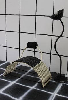 rubber and powdercoated metal low chair and bent tube and cement lamp