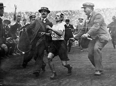 A racing clerk assists the Italian runner Dorando Pietri across the finish line in the marathon, at the White City stadium. Pietri was first past the post after taking a wrong turning and receiving medical attention for a fall. Although disqualified, he received a gold cup for his efforts from Queen Alexandra
