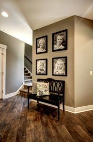 black and white family pictures in black frames on the khaki toned wall