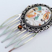 Small antique-silver-colored hair comb. The setting has a pretty edge. The handcrafted glass-cabochon shows a nice motif with fantasy-flowers.   The hair comb measures 5,6 L cm x 2,9 W cm.