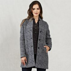A modern Donegal Tweed coat, featuring raglan sleeves and a cut away collar. The fabric is made with the finest pure new wool with a geometric grey and navy design. Styled with a Liberty print Harriet silk top and Fahan trousers.