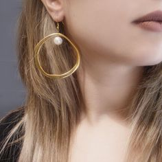 A stunning pair of earrings with a medium sized pearl, diam. 8 mm, hanging inside each hoop 5,6 cm diam. Total height of the earring, 6,5 cm. Available also in silver metal.  Warranty for 100%...