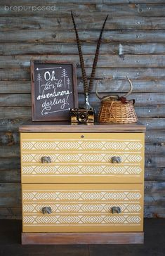 Here the amazing BrePurposed has used a base of Chalk Paint® by Annie Sloan in Arles, a rich, glowing yellow with an accent pop of Old White and an Aztec-style stencil to glorious effect! The elephant handles give a travelling feel as does the wood clad wall.