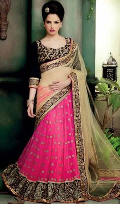 Get that chic look perfectly right with this beige and pink embroidered net lehenga saree. This beautiful saree is showing some astounding embroidery done with embroidery with stones crystals work. Upon request we can make round front/back neck and short 6 inches sleeves regular lehenga sari blouse also. #LatestEmbroideredLehengaSarees