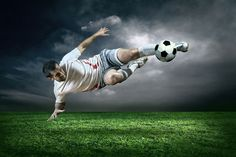 Soccer Action in Rain Wall Mural: Sports: Soccer: This action shot mural of a soccer player kicking the ball in mid air provides an intense energy with the stormy gray background. Any wall mural image that you choose can be printed on demand. Your specifications will be met for any interior design or home decor project. Create your own wallpapers, wall art and more by exploring our football, soccer, baseball, basketball and extreme sports collections.