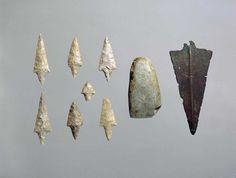 punte di freccia in selce, ascia in pietra levigata e pugnale in metallo