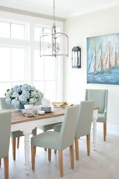 dining chairs Large dining room windows invite lots of light shining on a white dining room table with a wood top embellished by blue floral arrangements. White Dining Room Table, Dining Room Windows, Dining Room Lighting, Beach Dining Room, Blue Dining Rooms, Light Wood Dining Table, White Wood Table, Dining Room Table Centerpieces, Dining Nook