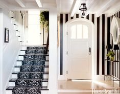 In the foyer, the classic design is jazzed up with black-and-white striped walls and a zebra print runner on the stairs.