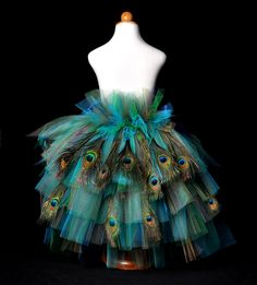 The girls and teen size Peacock Bustle Tutu is stunning in shimmering gold, turquoise, navy and emerald green tulle, and features a gorgeous feathered bustle. The tiered bustle is adorned with 14-16 peacock eye feathers depending on size ordered. This tutu will come with two satin