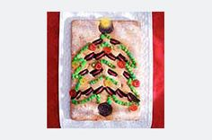 Festive Tree Cake Recipe >>>> Chocolate sandwich cookies are baked in a tree shape over cake batter. The cookie tree is then decorated with icing and candies for a festive dessert.