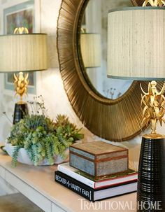 Brass lamps, a textured mirror frame, and a marble bowl overflowing with succulents garnish the console table. - Traditional Home ® / Photo: John Merkl / Design: Hillary Thomas