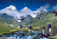 Trekkers cross the outlet stream of Lake Carhuacocha (13,600 feet) in the Cordillera Huayhuash, Andes Mountains, Peru, South America. On the left, Yerupaja Grande (east face, 6635 m or 21,770 ft) is the second-highest peak in Peru, highest in Cordillera Huayhuash, and highest point in the Amazon River watershed.