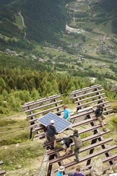 Volunteers install a photovoltaic solar power plant on avalanche barriers in the ski resort of Bellwald.