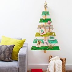 Pallet Christmas Tree - To make, draw a large triangle on a large shipping pallet to desired size (ours is 44-inches tall). Cut out the triangle using a jigsaw; use sandpaper to smooth all surfaces. Paint tree slats with alternative shades of green paint. Predrill holes, then screw small cup hooks and drawer pulls to the front. Hang cards and decorations on the cup hooks. Tie rope between knobs; attach clothespins to rope. Garlands, globe lights, and mini presents also make fun tree…