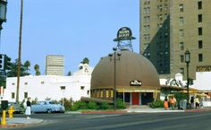 """There is something about the original Brown Derby restaurant on Wilshire Blvd that epitomizes golden-era Hollywood for me. And when I find a color shot of the place, it allows me to slip more easily into imagining what it must have been like to walk through that red door and """"eat in the hat."""" (And in my mind, I'd probably be driving the powder blue car parked on Alexandria Ave.)"""