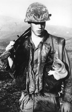 A soldier of the U.S. Seventh Marines carries a rescued puppy in his pocket. Da Nang, Vietnam, 1968.