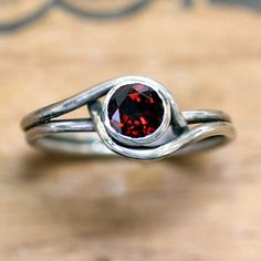 A gorgeous red garnet glows in my unique recycled sterling silver setting that has gorgeous movement and modulation. This beautiful ring is a smaller