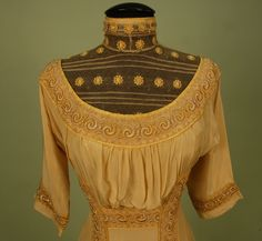 Front Detail YELLOW SILK EMPIRE GOWN with EMBROIDERED NET, c. 1912. Butter yellow crepe with high neck bodice insert of cotton net embroidered with flowers, elbow length sleeve, bodice and skirt decorated with net bands having scrolls of padded embroidery, front and back vertical bands with silk tassels, silk lining, back hook & eye closures.