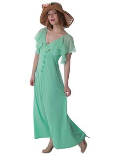 <p>Romantic 30s inspired look from the 1970s in mint green jersey with chiffon capelet flutter sleeves and flower accent. Lovely look for a summer garden wedding.<br /><br />Pair with a wide brimmed hat, strappy peep toe heels and a delicate choker.<br /><br />DETAILS<br />•Authentic, one of a kind vintage from the 70s era.<br />•Soft drapey poly jersey fabric in mint green.<br />•Sle...