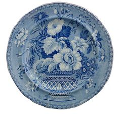 "Botanical Vase - Minton  Found on a 9.75 inch pearlware plate, this pattern has the factory name, ""Botanical Vase"". There are many patterns that are similar by other makers. The vase and its large bouquet of flowers are printed against a beaded medium blue ground. The only border is the stringing at the edge of the plate. The pattern, circa 1820, is found on dinnerware, toilet ware, and tea ware. There are various designs in this pattern, each featuring differing floral arrangements. The…"
