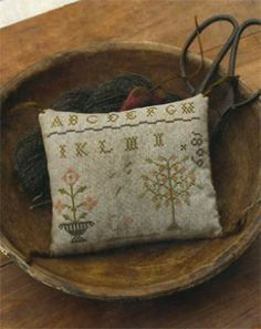 """""""1809 Schoolgirl Pincushion"""" is the title of this cross stitch pattern from Stacy Nash Primitives."""