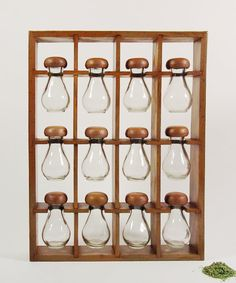 mid-century hanging spice rack for your retro kitchen.  A strong, somewhat rustic wooden frame - designed to be hung on a wall - holds twelve matching curvy glass bottles with screw-on mushroom shaped resin caps. The 12 jars nestle into grooves on the front and will make a beautiful display when filled with spices. It could be used to sort and display beads too! Or small hardware.