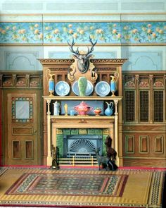 THE DINING ROOM 1894 The fireplace wall features natural woodwork surrounding the tiled fireplace box surmounted by an overmantel with shelves laden with ornamental china; towering over all is a mounted stag head with sets of smaller horns below; on one side a passageway door leads to the kitchen while on the other, there may be a dish-storage area shielded by screening; the effect is rich and colourful