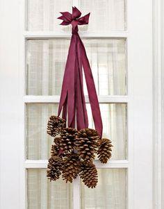 Think outside the circle. 8 four to six inch pinecones and 8 two-foot-long pieces of silk ribbon. Hot glue the last 2 inches of each ribbon to pine cone base. Once glue dries, gather ends, stagger so cones fall at varying lengths. Tie ribbons together in knot, trim ends to more uniformed look and slip over finishing nail.