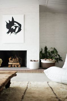 White painted brick fire place inside a minimal style in this updated mid-century living room | house tour on coco kelley