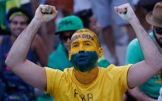 Um homem com o rosto pintado acompanha a sessão especial que vota o processo de impeachment da presidente Dilma Rousseff em um telão instalado na praia de Copacabana, no Rio de Janeiro