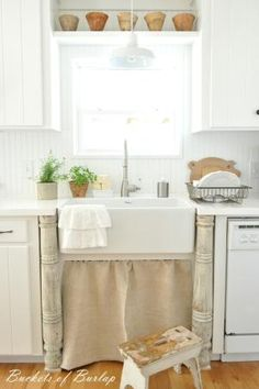 Farmhouse kitchen. Painted white countertops and grainsack sink skirt by trudy