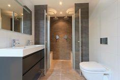 Één van onze showroom badkamers. Tegels, badmeubel, toilet, modern. Inbouw douche.