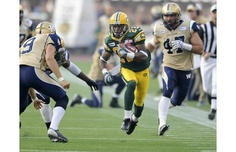 Edmonton Eskimos' Joe Burnett, centre, runs through Winnipeg Blue Bombers' Mike Renaud, left, and Pierre-Luc Labbe during their CFL game in Edmonton on Friday, July 13, 2012.