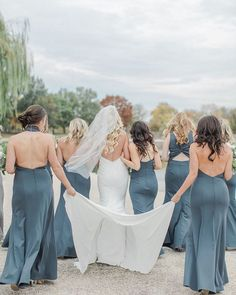Chic bridesmaids in the Petra dress by Jenny Yoo - a sleek fit & flare silhouette with a modern halter neckline in our form-fitting & flexible Knit Crepe. A sophisticated high neck iscomplemented by the backless bodice. A defined waist seam perfects the fit, while princess seams in the skirt provide a dramatic sweep. Petra makes a great guest of wedding or any fall / winter occasion dress! Shown in Mayan Blue. @dyannalamora