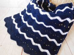 This soft crocheted baby blanket is made with a lace affect and with navy blue as a main and some white stripes. This is a chevron type pattern but with more of a ripple effect. This blanket woul...