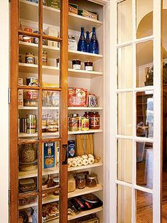 The kitchen pantry has many shelves encased by paned French doors.
