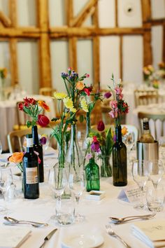 Supermarket table flowers in recycled glass bottles. . Photography by Caro Weiss #wedding #flowers #tablecentres