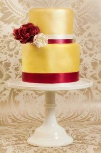 Arabella is a beautiful trendy 4 tier gold and burgundy cake set off with elegant large sugar roses. Wonderful for a winter or golden wedding.