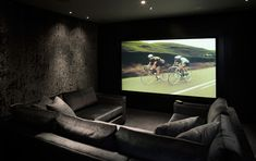 I like this simple cinema room. I like the dark colours and the velvet wall and the large tv screen.