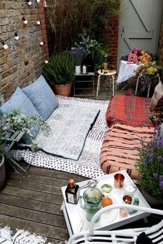 Blankets and poufs and lots of plants mkae this little patio, spotted on Decorist, extra inviting.