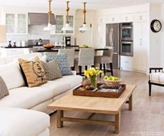 The weathered floors lend a casual, rustic vibe to this open living room and kitchen. Read more at http://bhgrelife.com/flooring-options-for-your-home-living-room-ideas/