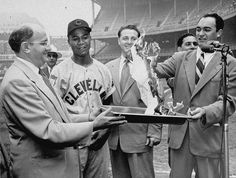 Larry Doby of the Cleveland Indians smiles as radio announcer Mel Allen (right) gives the slow burn to the $3,500 mortgage on Larry's home in Paterson, N.J., during