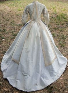 """Reception Dress 1865, silk moire trimmed w/handmade torchon lace. Long lappets on collar rear - 1865/66 trend. Lace-trimmed belt, self-fabric rosette. Sleeves have self-fabric petals at tops trimmed with lace & accented w/clear glass dangles. Same bobbles on bodice front, non-functioning. Bodice closes w/hooks & eyes. Piped armholes. Fully lined w/white muslin. Grey wool hem tape. Left front closure. Pocket right side seam, watch pocket in waistband. bust 34"""" waist 26, skirt circ 205"""""""