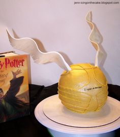 Harry Potter Snitch cake. Fondant/gumpaste wings. Cake is covered in buttercream with buttercream details.
