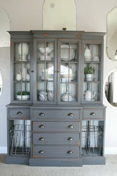 A dark grey painted hutch with white ironstone, wire baskets and grain sack stripe painted interior..