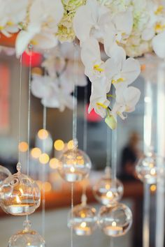 Tea lights flickered in glass orbs suspended from a magnificent arch of vanilla orchids and hydrangeas at the couple's all-white reception. #centerpiece Photography: Vanessa Joy Photography. Read More: http://www.insideweddings.com/weddings/a-bright-modern-summer-wedding-with-mint-coral-details/648/