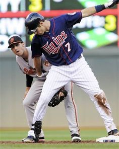 Baltimore Orioles second baseman Ryan Flaherty, left, makes sure Minnesota Twins' Joe Mauer remains on the base after Mauer doubled in the first inning of a baseball game, Tuesday, July 17, 2012, in Minneapolis