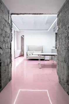 Office design by Crosby Studios - Hege in France raw concrete walls pink floor grey sofa